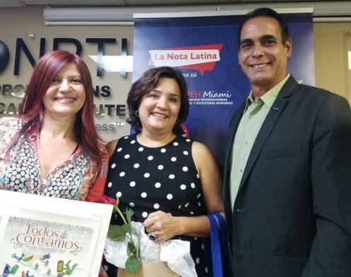 """Albert Collazos, director de comunicaciones Hispanas de la Ford, entrega reconocimiento a Patricia Rebellón, por """"El Palo de Mamoncillos"""", mejor su cuento ambientalista."""