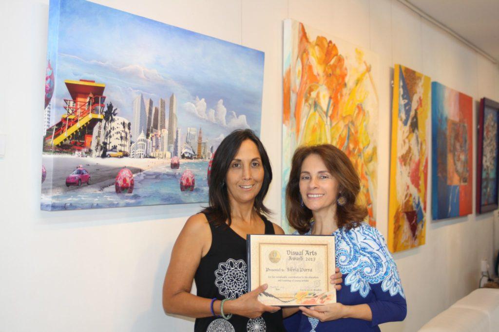 Maritza Salcedo, presidenta de Almenar Otero Foundation, hace entrega del galardon a la artista Silvia Parra.